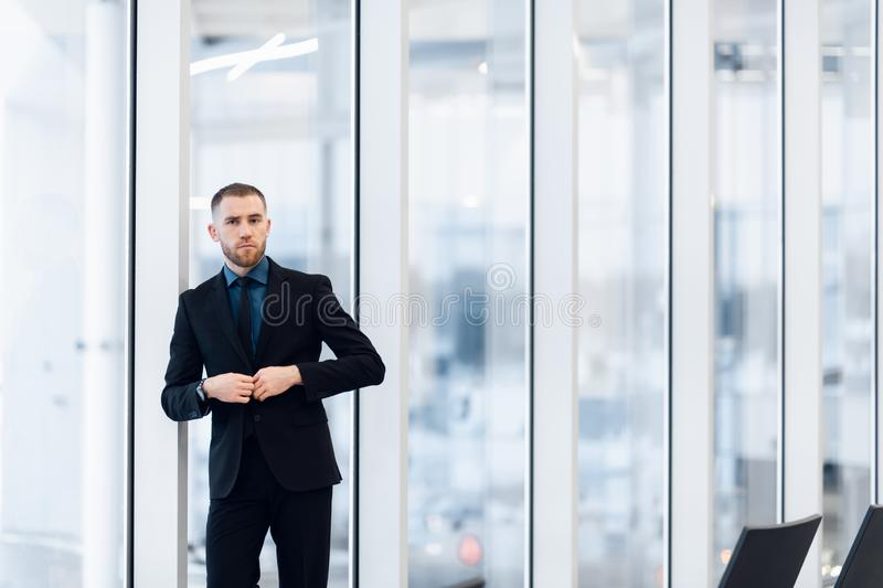 Stylish young businessman wearing a modern suit, who is a high achiever, standing on the top floor of an office building. Looking out at the view through large royalty free stock images
