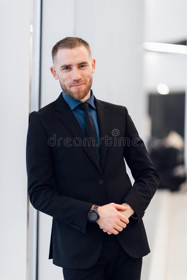 Stylish young businessman wearing a modern suit, who is a high achiever, standing on the top floor of an office building. Looking out at the view through large stock photography