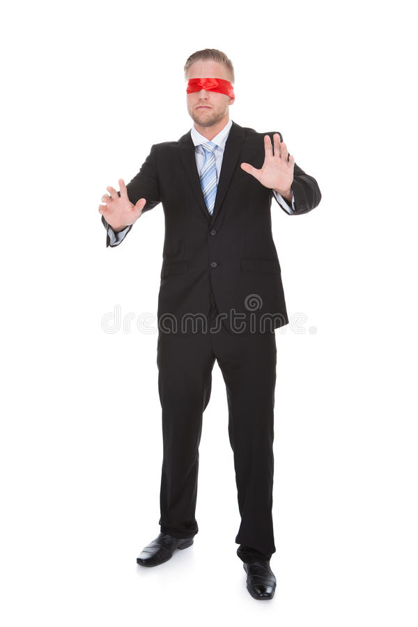 Stylish young businessman wearing a red blindfold. Stretching his hands out in front of him to feel for unseen obstacles full length isolated on white royalty free stock images