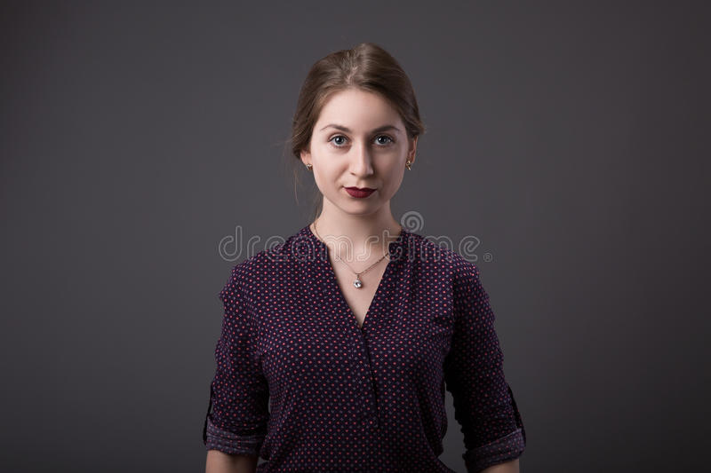 Stylish young businesswoman with a friendly expression looking directly at the camera, closeup of her face on a grey stock image