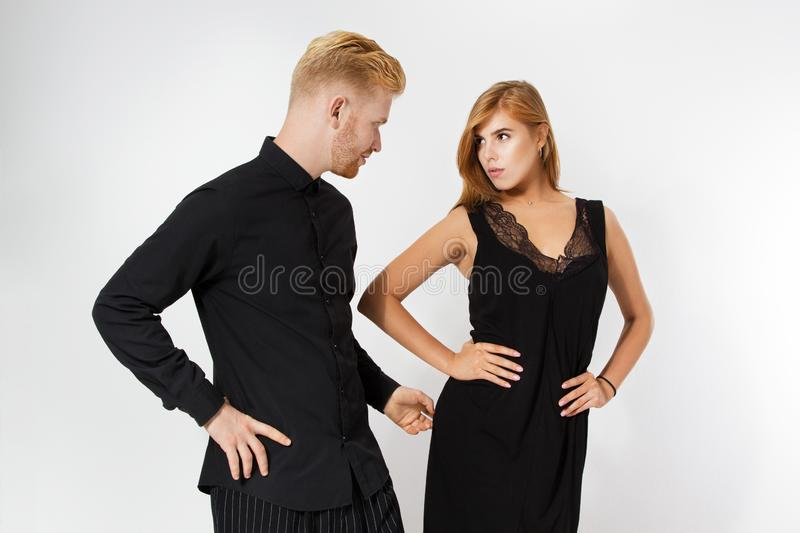 Stylish young couple in black  over white. Couple looking at each other royalty free stock photos