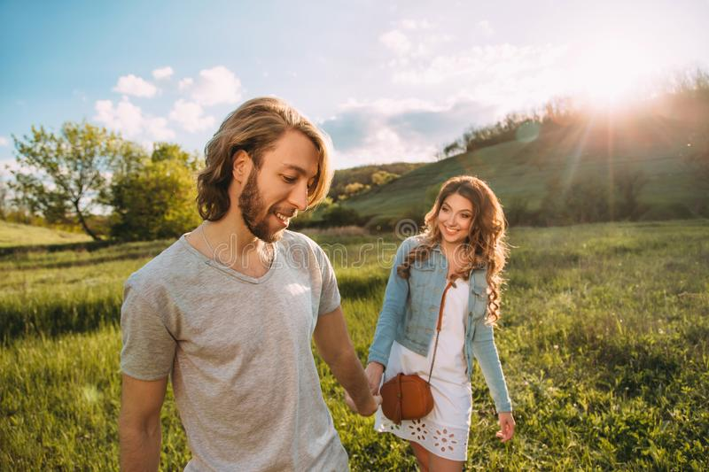 Stylish young couple. Film photo at sunset and with a sunlight. A guy with a stylish haircut pulls by the hand and a red. Haired girl. Lovers run and laugh stock image