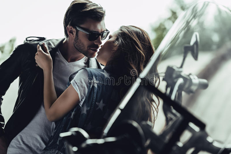 Stylish young couple hugging and kissing on motorcycle outdoors. Beautiful stylish young couple hugging and kissing on motorcycle outdoors stock images