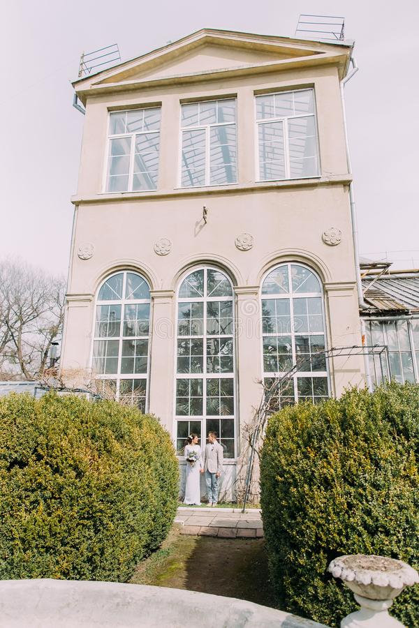 Stylish young couple near the old beige house with columns and big vintage windows. Romantic wedding in Paris royalty free stock images