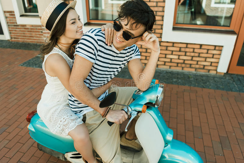Stylish young couple riding scooter together stock image