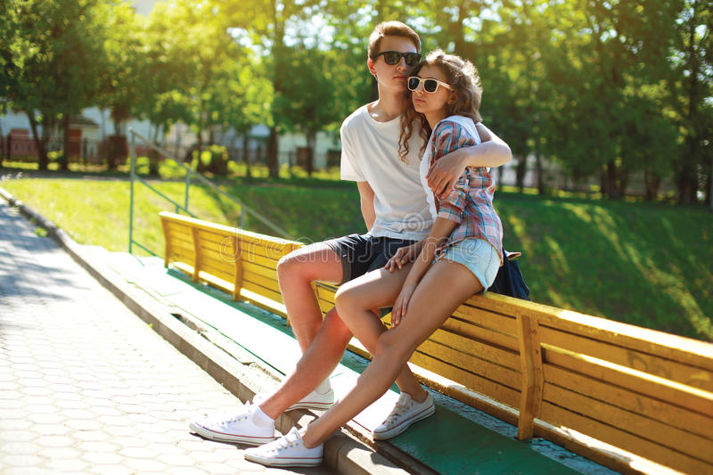 Stylish young couple teenagers sitting on the bench city, summer day royalty free stock photo