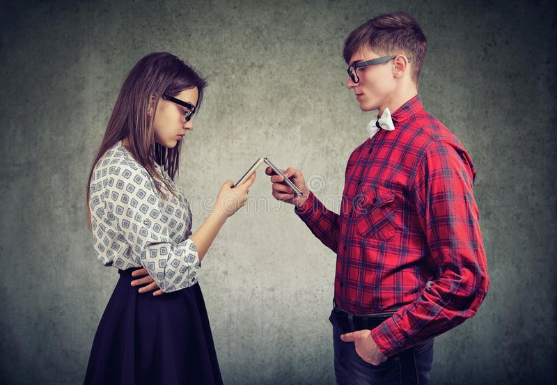 Couple using smartphones totally absorbed in online life, not talking to each other, facing one another. Stylish young couple using smartphones totally absorbed stock photography