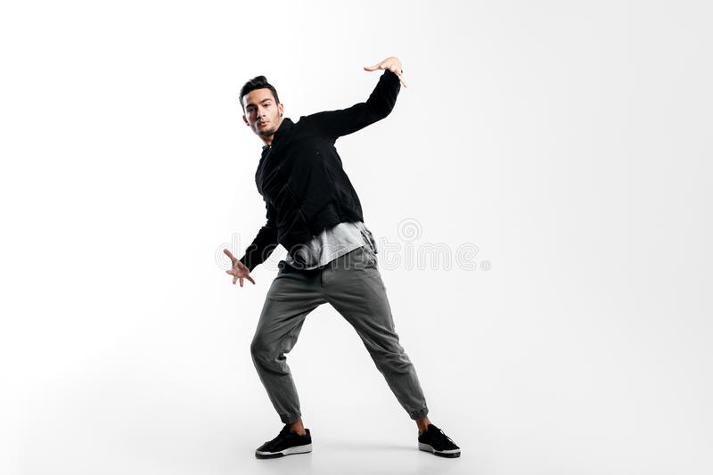Stylish young dancer wearing a black sweatshirt and gray pants is dancing hip-poh on a white background stock photos