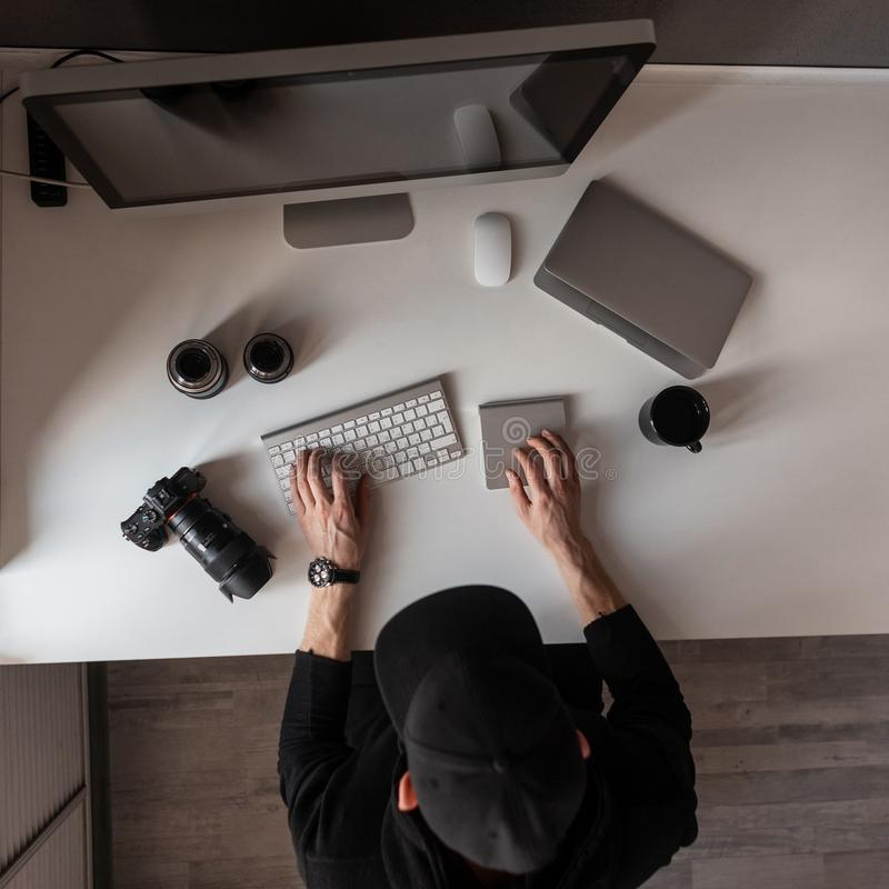 Stylish young designer working at a white desk. Top view of the person in the cap and on the desktop on which there is a keyboard. Camera, laptop and royalty free stock images