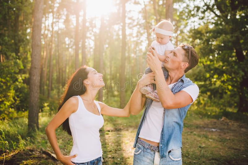 Stylish young Family mom, dad and daughter one year old blonde sitting with father on shoulders playing happy and smiling, royalty free stock photography