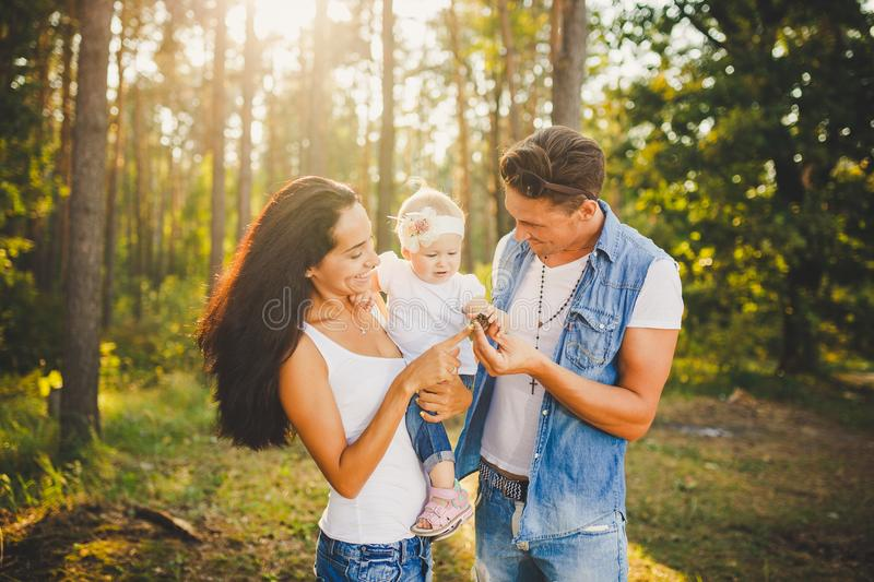Stylish young Family mom, dad and daughter one year old blonde sitting with father on shoulders playing happy and smiling, outdoor. S oute the city in the woods stock image