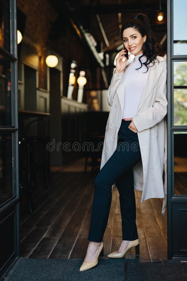 Stylish young female with dark hair wearing white coat, black tr. Ousers and shoes with heels posing into camera while standing against cafe background chatting royalty free stock images