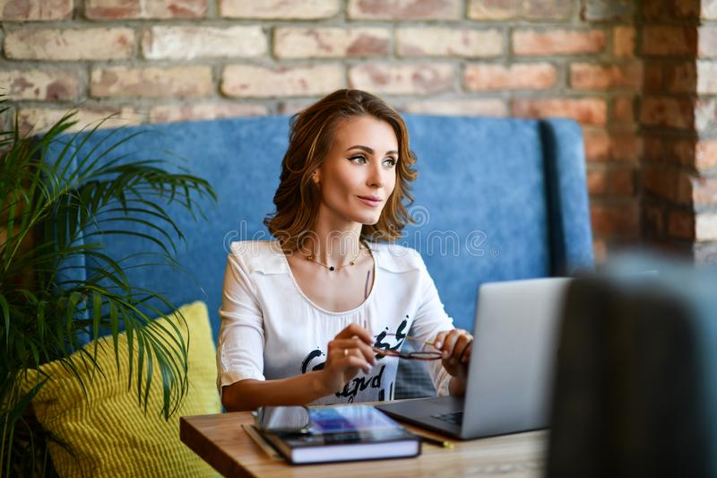 Stylish young girl businesswoman working in a cafe at the computer. Coffee break royalty free stock photo