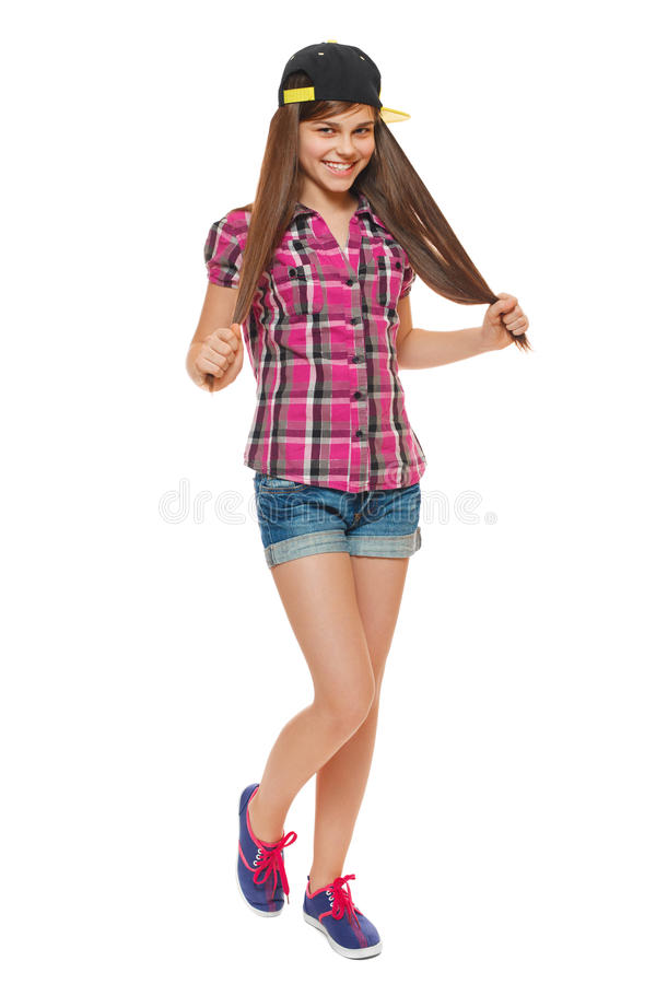 Stylish young girl in a cap, a shirt and denim shorts. Street style teenager, lifestyle, isolated on white background stock photo