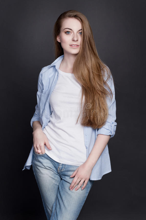 Stylish young girl in denim clothes. She is cheerful and energetic royalty free stock photos