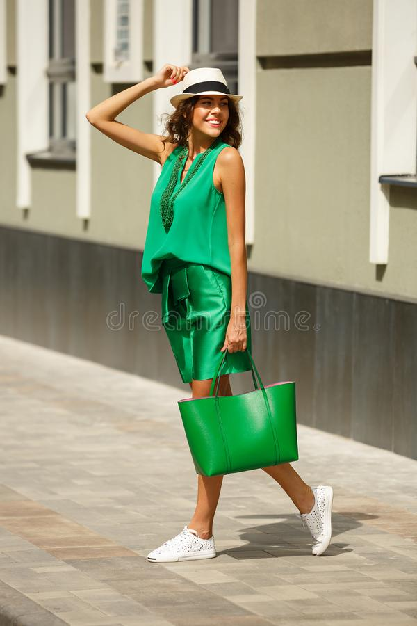 Stylish young girl dressed in green fashion summer suit, white hat and white sneakers poses in the street on a sunny day stock image