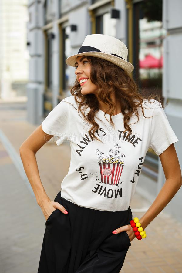 Stylish young girl dressed in a white t-shirt, black wide trousers and white hat poses in the street on a sunny day royalty free stock photo