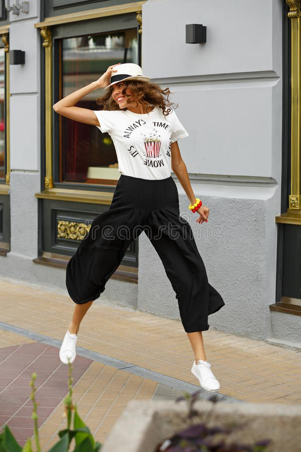 Stylish young girl dressed in a white t-shirt, black wide trousers and white sneakers is jumping in the street on a stock photography