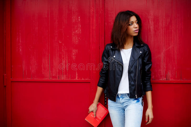 Stylish young girl in a leather jacket standing against a red fence with a book in their hands. Attractive afro american female posing on red wall background in stock photo