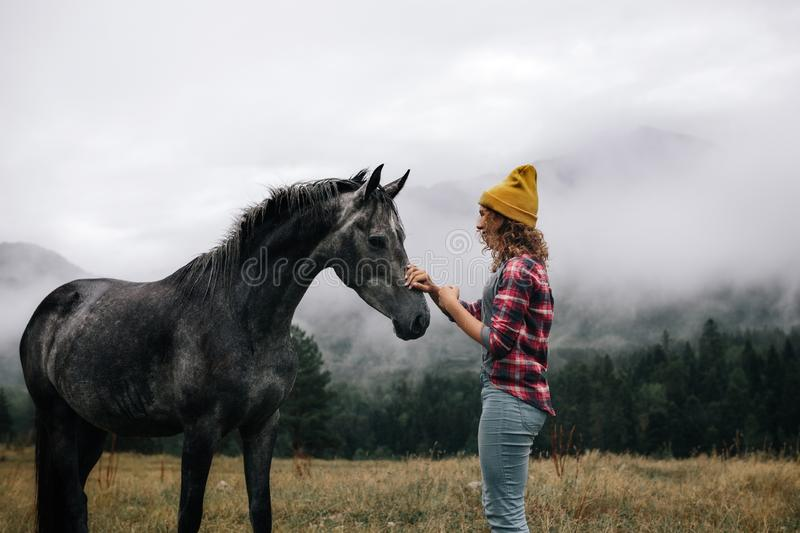 Stylish girl look and caress the horse over mountains in the fog royalty free stock photo
