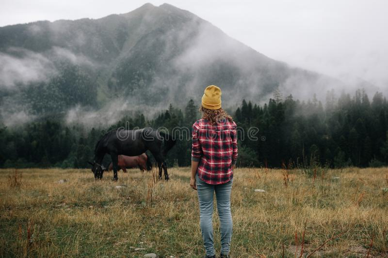 Stylish girl look at the horse over mountains in the fog royalty free stock photo
