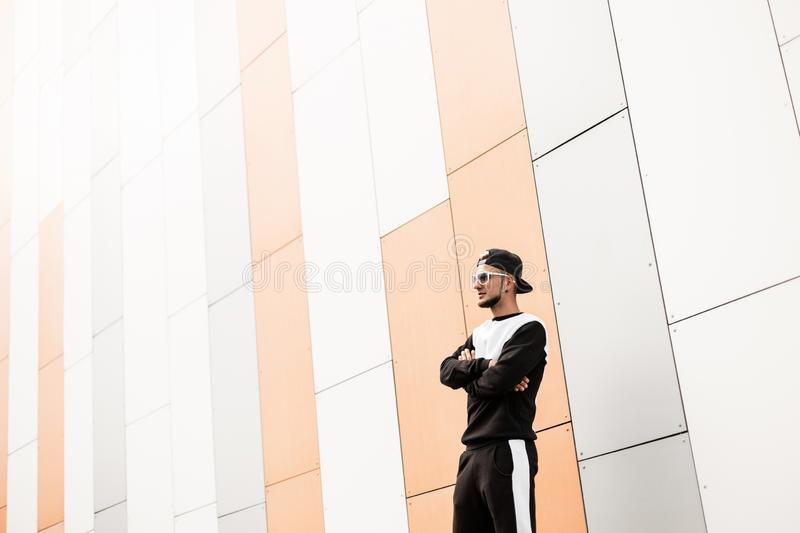 Stylish young hipster man in stylish cap in sunglasses in trendy black sports suit is standing near a modern building in the city. On a bright sunny day royalty free stock photography