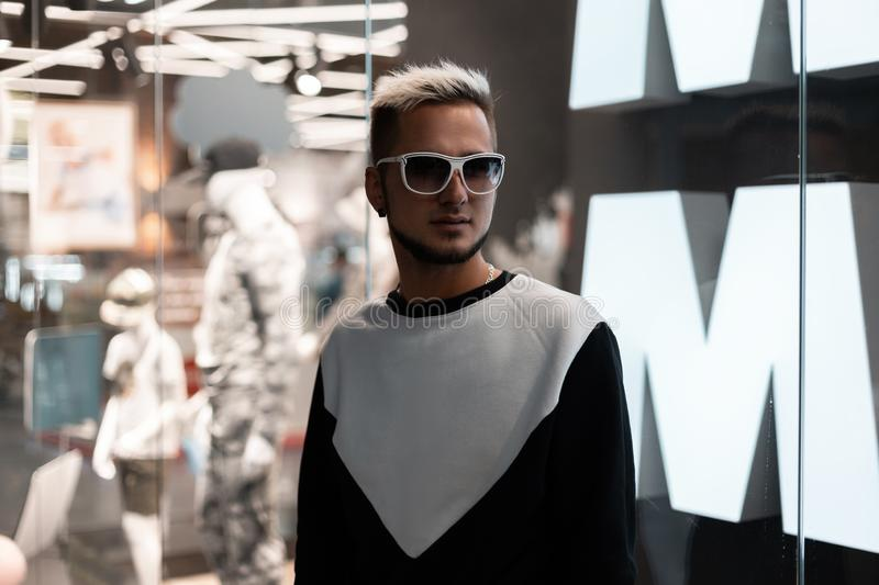 Stylish young hipster man with trendy hairstyle in black and white sweatshirt in fashionable sunglasses. Stands in a modern shopping center near the glass wall royalty free stock photography