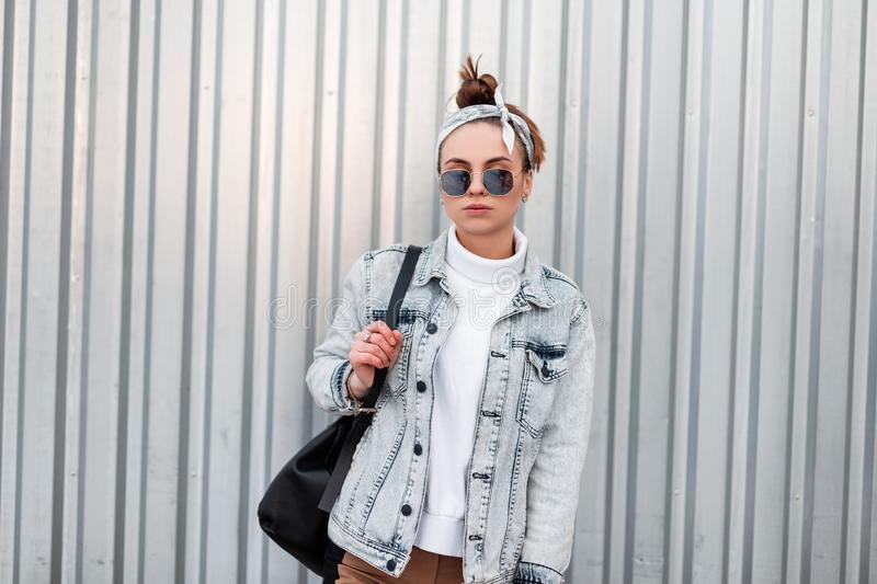Stylish young hipster woman in sunglasses in trendy bandana in summer denim jackets in a knitted sweater royalty free stock photo