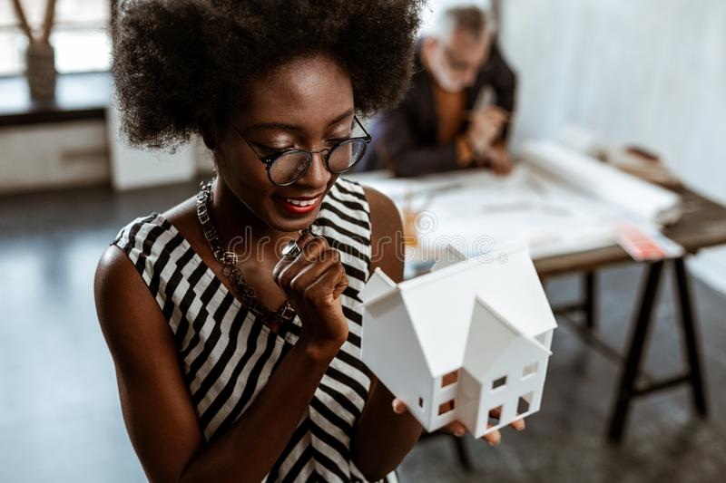 Stylish young interior designer looking at little house model. Looking at model. Stylish young interior designer wearing stylish jewelry looking at little house stock photography