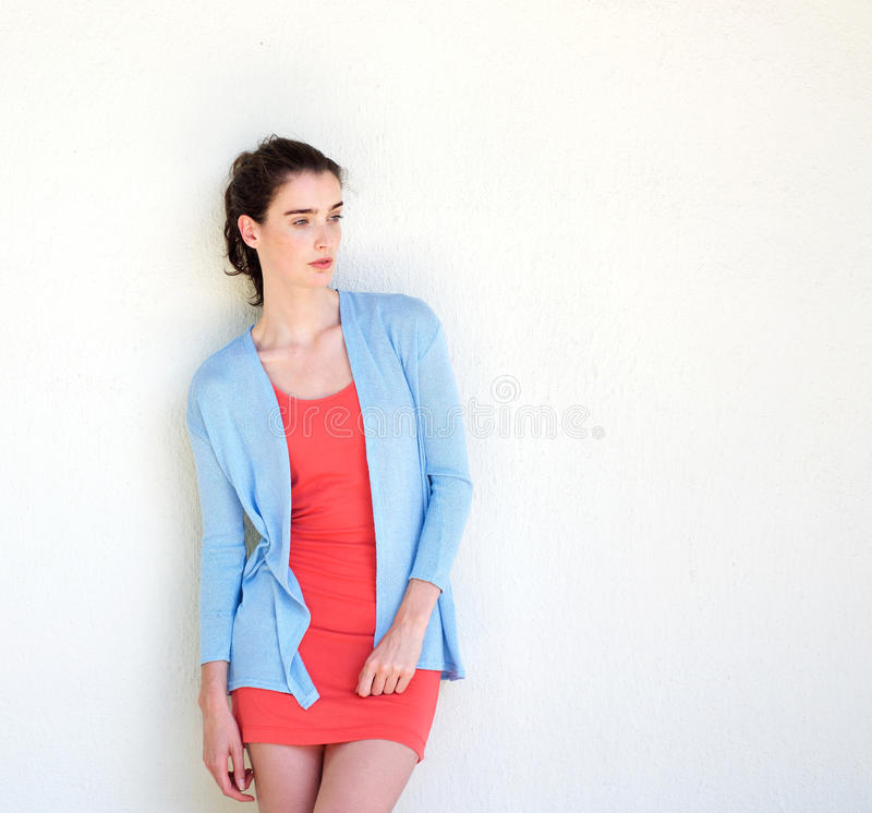 Stylish young lady standing against white wall stock photography