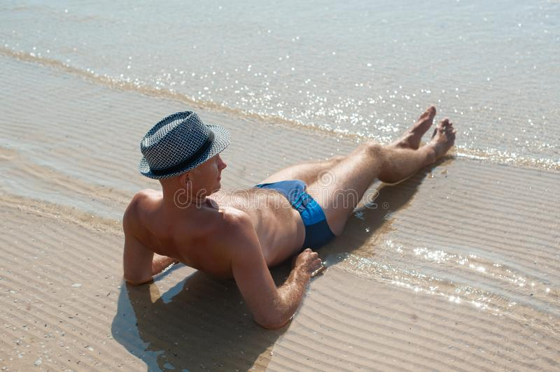 Stylish young male model man lying on beach sand wearing hipster summer hat enjoying summer travel holiday near the sea stock photography