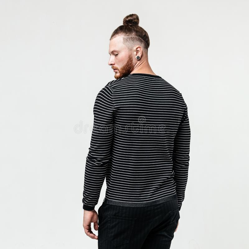 Stylish young man with beard and bun hairstyle wearing a dark striped jumper and trousers poses poses in the studio on royalty free stock images