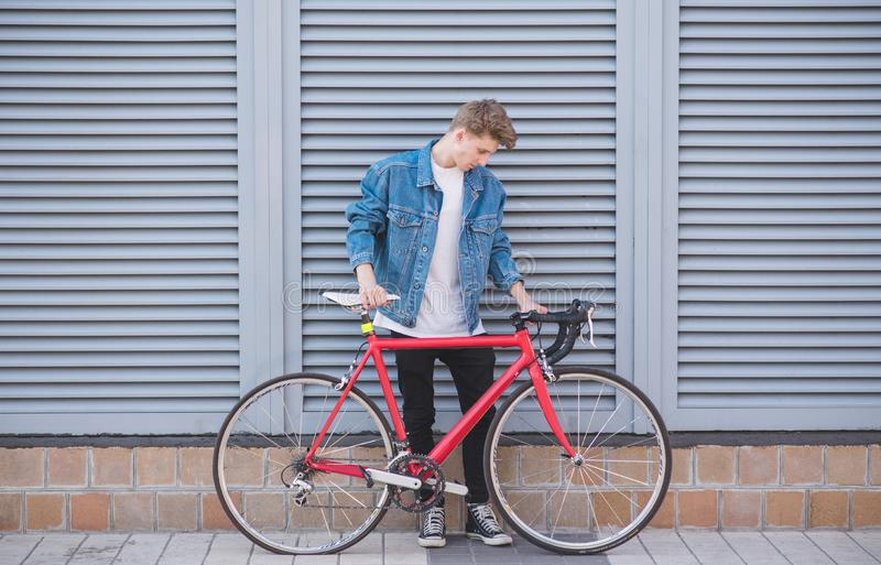 Stylish young man with a bike in which the pierced wheel is standing against the background of the wall royalty free stock photography