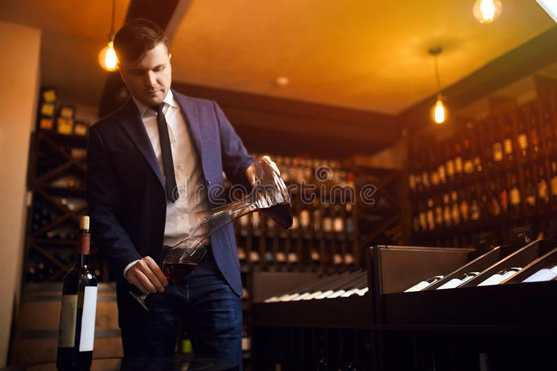 Stylish young man in blue suit and white shirt pouring wine from decanter stock image