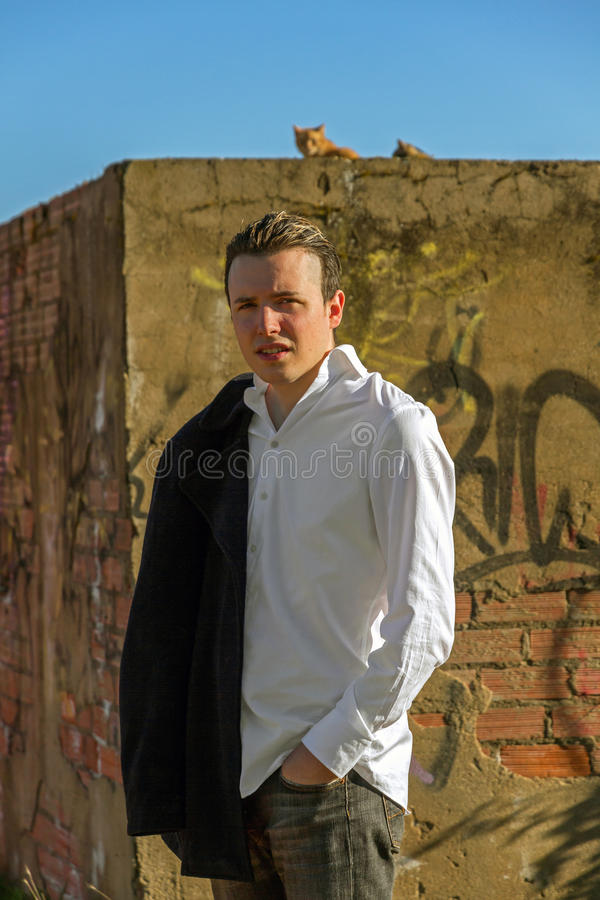 Stylish Young Man with Cats and Graffiti. Smart young man, outdoors, white shirt and jacket hanging man, bottom painted brick wall with graffiti and cats at the royalty free stock photos
