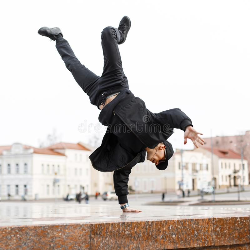 Stylish young man dancer in black jeans in a stylish jacket in a cap in sunglasses does a handstand in the city on the street royalty free stock photography