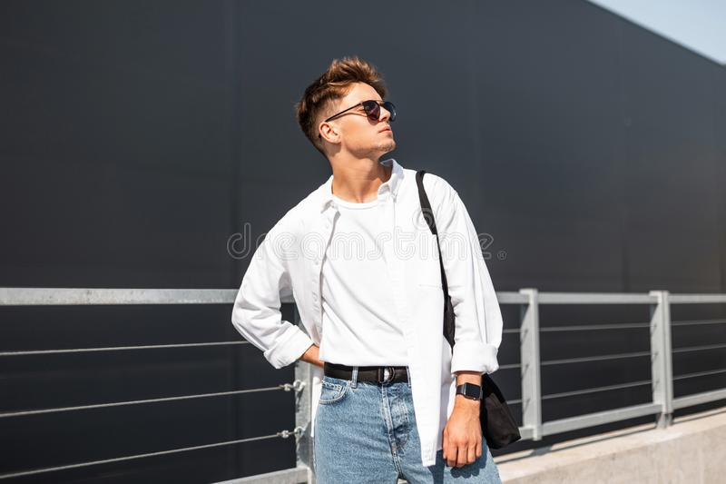Stylish young man hipster in dark sunglasses in white fashionable clothes with trendy hairstyle with bag posing. Near a modern building on a sunny day outdoors stock photography