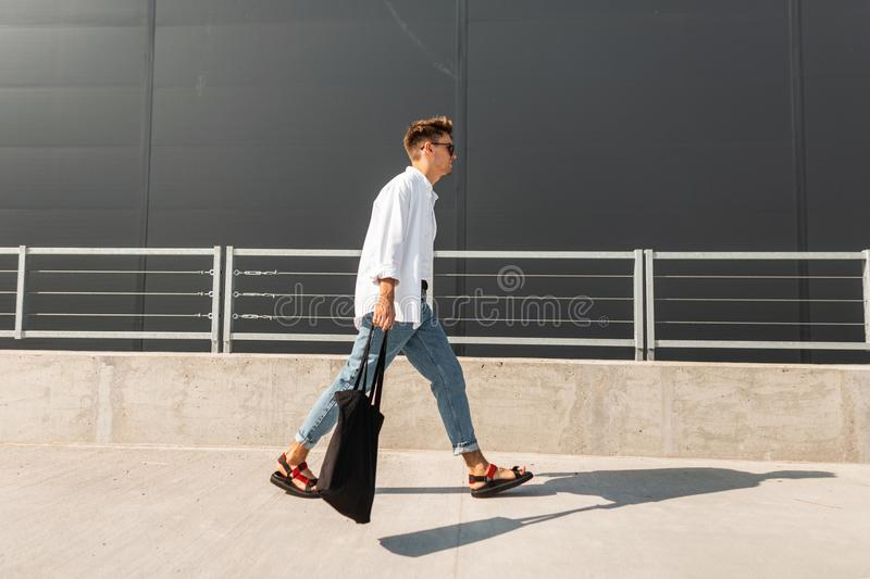 Stylish young man hipster in fashionable clothes in leather sandals with a fabric bag in sunglasses walks on the street. Near a gray building. Trendy urban guy stock photo