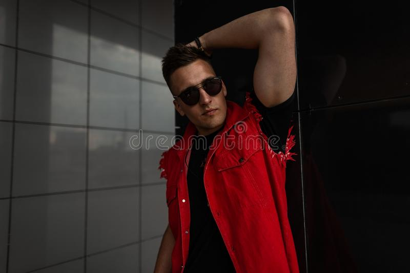 Stylish young man hipster in a red trendy denim vest in a black T-shirt in sunglasses posing near the gray wall on the street. Modern urban guy model in the stock photo