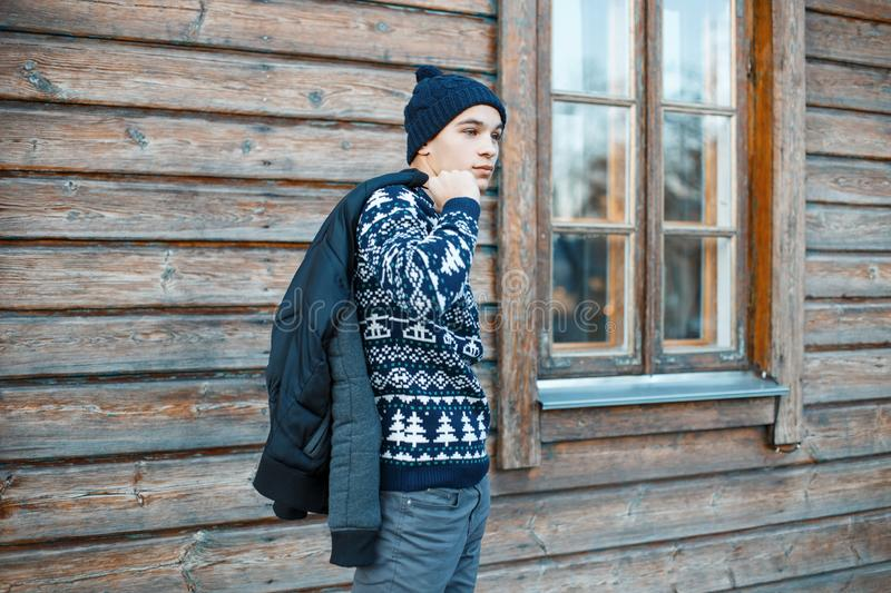 Stylish young man in a knitted blue hat in a vintage sweater with a white Christmas pattern in trendy jeans with a winter jacket. Standing near a wooden brown royalty free stock photo