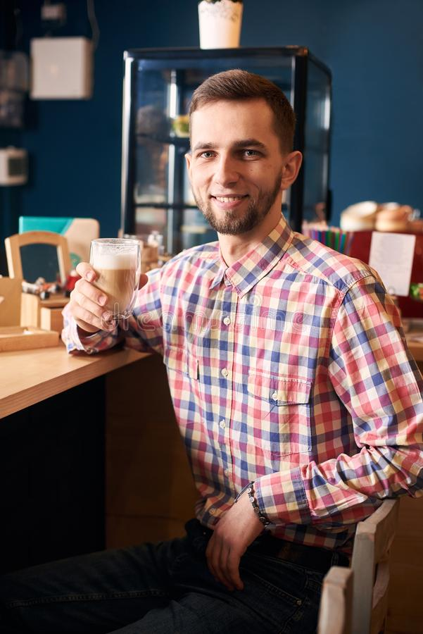 Young bearded man sitting in cafe and smiling in camera, holding cup of latte coffee. Portrait shooting. Dark background stock photography