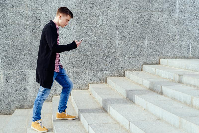 Stylish young man in plaid shirt and jeans walking up stairs. stock image