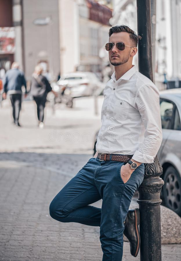 Stylish young man posing in outdoor stock photos