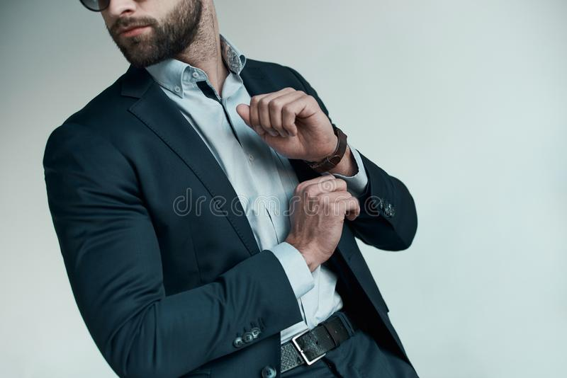 Stylish young man in a suit. Business style. Fashionable image. Evening dress. Serious man standing and looking aside. Fashion look. Gray background. Close-up stock image