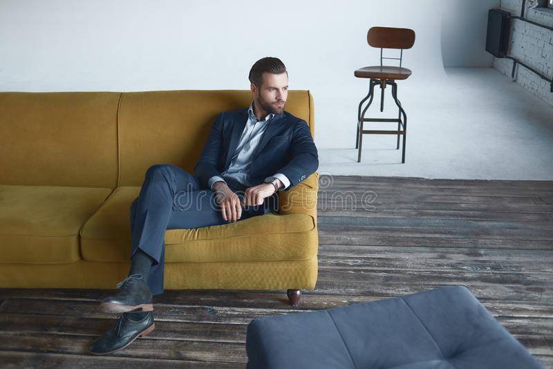 Stylish young man in a suit. Business style. Fashionable image. Evening dress. man standing and looking at the. Stylish young man in a suit and bow tie. Business stock photos
