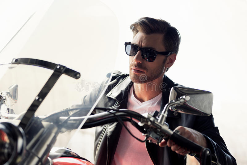 Stylish young man in sunglasses and leather jacket sitting on motorcycle and looking away stock images