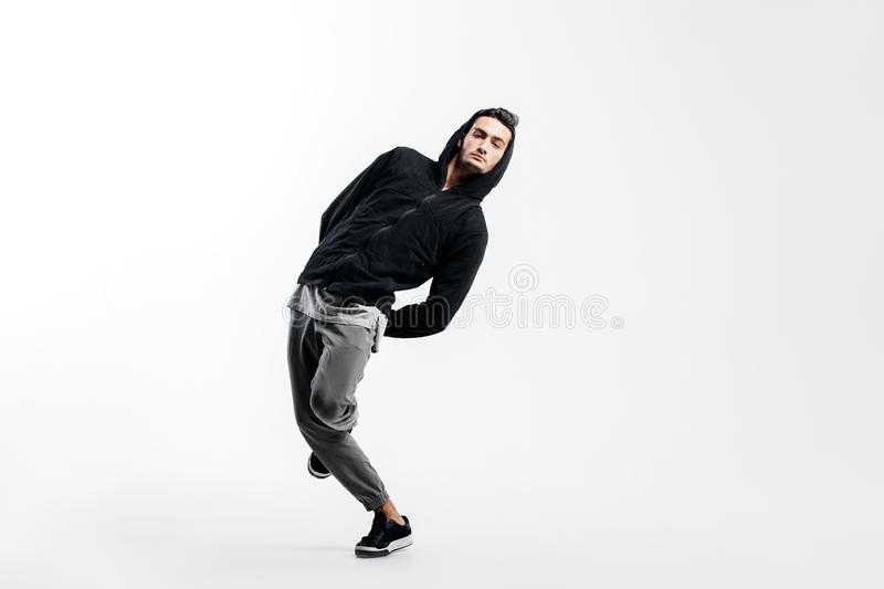 9e050886 Stylish young man wearing a black sweatshirt and gray pants is dancing  street dances on a