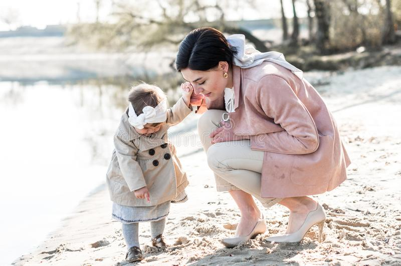 Stylish young mother on a walk with her baby daughter on a sandy shore. Near the water stock photos