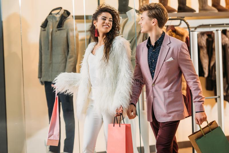 stylish young multiethnic couple with shopping bags walking together royalty free stock images