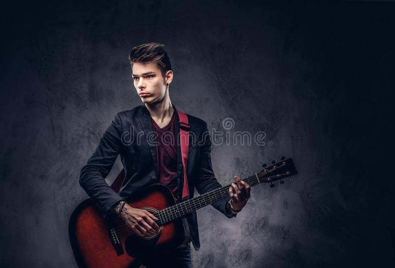 Stylish young musician with stylish hair in elegant clothes, playing on an acoustic guitar. Handsome young musician with stylish hair in elegant clothes with a royalty free stock images